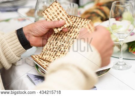 Jewish Family Celebrating Passover.jewish Man Blessing And Breaking Matzah As They Celebrate Seder.