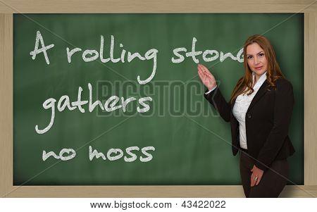 Teacher Showing A Rolling Stone Gathers No Moss On Blackboard