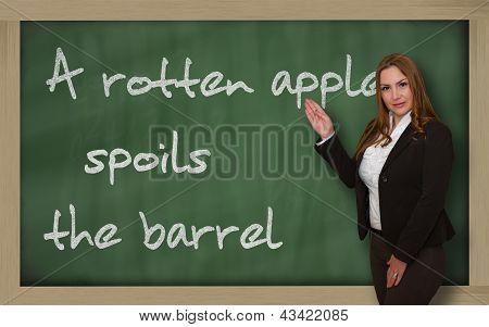 Teacher Showing A Rotten Apple Spoils The Barrel On Blackboard