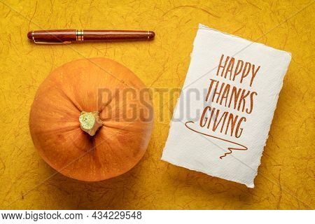 Happy Thanksgiving - handwriting on white Khadi paper with a pumpkin and a stylish pen, holiday greeting card
