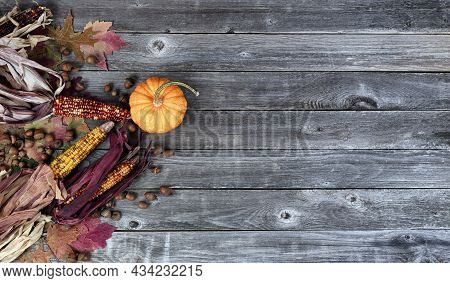 Overhead View Of Real Whole Pumpkin, Corn, Acorns And Foliage Leaves On Weathered Wooden Planks For