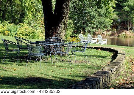 Picturesque Setting Showing Metal Table And Chairs, Stonewall, And Three Adirondack Chairs On The Sh