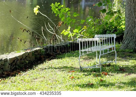 White Metal Park Bench Sitting Under A Shade Tree Along A Stonewall Bordering A Small Lake.