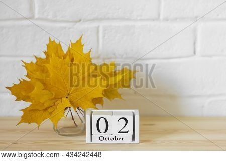 October 2 On The Calendar And A Bouquet Of Bright Autumn Leaves On The Table.one Of The Days Of The