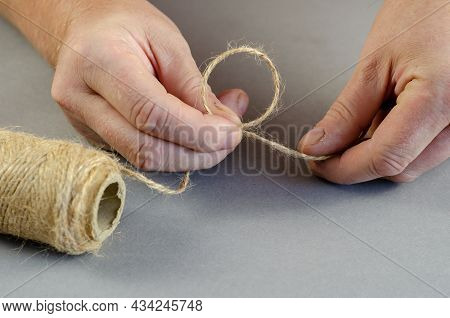 Two Hands Tie A Knot Of Twine On A Gray Background. Quiver Is A Thin Thread That Is Made By Twisting