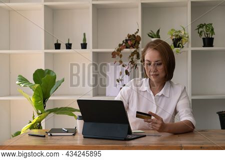 Middle Asian Woman Doing E-shopping With Credit Card And Laptop Computer, Online Purchase Concept