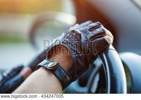 The Drivers Hands In Leather Gloves Driving A Moving Car. Woman Holding Steering Wheel In Racing Glo