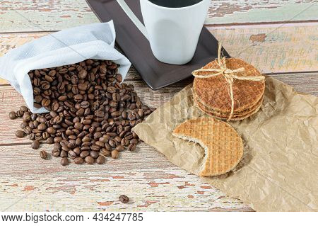 Stroopwafel Cookies With A Bite Next To Beans And Cup Of Coffee.