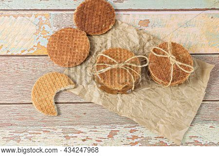 Stack Stroopwafels On Brown Paper, Next To Another Biscuit With A Bite.