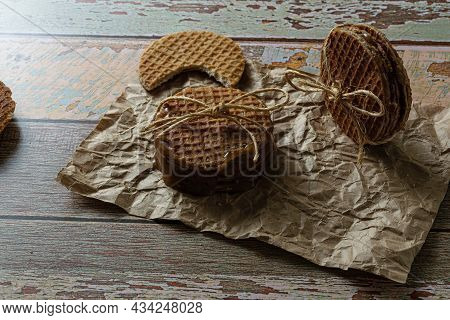Low Key Photography. Stacking Stroopwafels With A Sisal Bow, Next To Another Biscuit With A Bite.