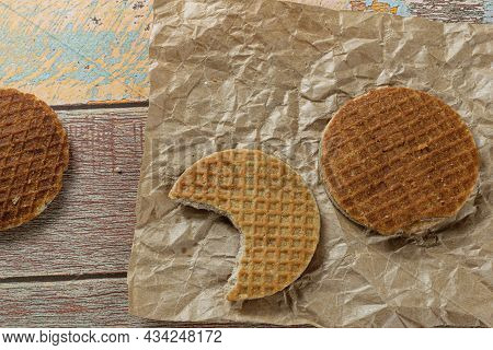 Stroopwafel With A Bite On Brown Paper Next To Another Cookie (top View).
