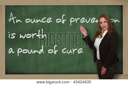 Teacher Showing An Ounce Of Prevention Is Worth A Pound Of Cure On Blackboard