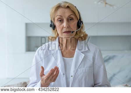 An Experienced Elderly Female Doctor Who Talks Into The Camera And Gives Online Medical Advice In A