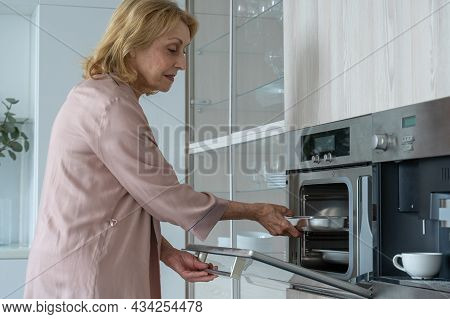 Smiling Elderly Woman Baking Pastries At Home, Taking The Pastries Out Of The Oven, An Elderly Lady