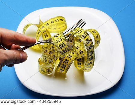 The Man Is Holding A Fork In His Hand. Measuring Tape Is Wound Around The Fork. Healthy Food, Calori
