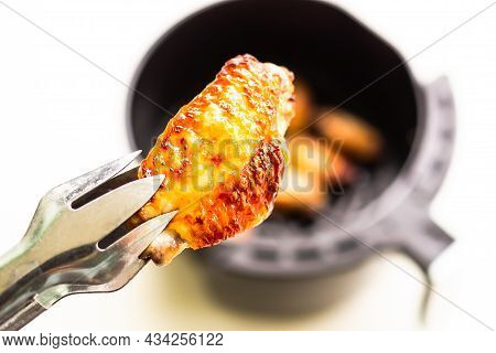 Baked Chicken Wings With Tongs On Blur Baked Chicken Wings In Air Fryer On White Table Background. C