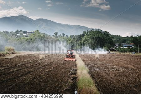 Farm Worker Drove Tractor For Tillage In Agriculture Fields. Farmer Working Soil Plowing Preparation