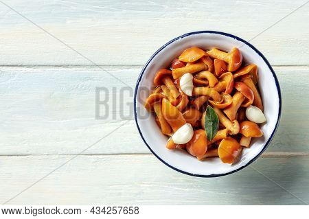 Pickled Mushrooms With Garlic And A Bay Leaf, Top Shot On A Rustic Wooden Background With A Place Fo