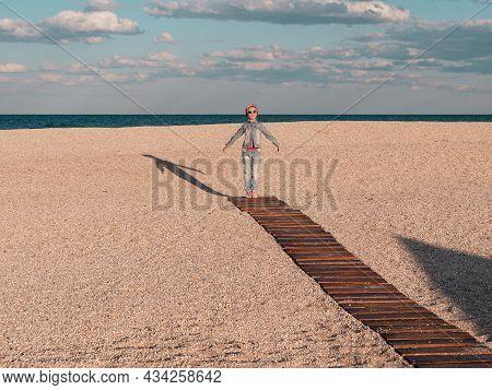 Happy Little Girl Walking Alone On Wooden Boardwalk On Seascape Background Blue Sky. Child Resting R