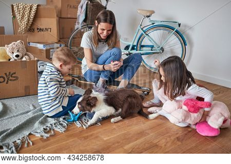 Young mother with kids and a pet in a family atmosphere is enjoying the new home they moved in. Home, family, moving