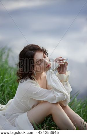 Beautiful Young Woman In White Dress Resting On Shore Lake Pond River. Professional Makeup And Hairs
