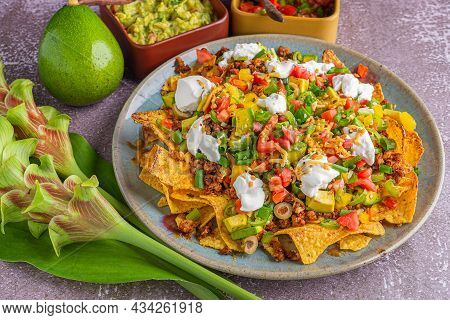 Close-up Of Loaded Minced Pork Nachos With Guacamole And Salsa Dips. Space For Text. Concept Of Mexi