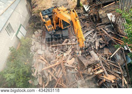 Process Of Demolition Of Old Building Dismantling. Excavator Breaking House. Destruction Of Dilapida