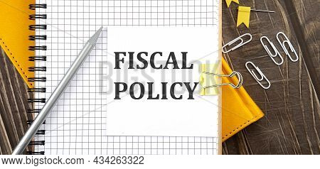 Fiscal Policy Text On A Sticker On Notebook, Wooden Background