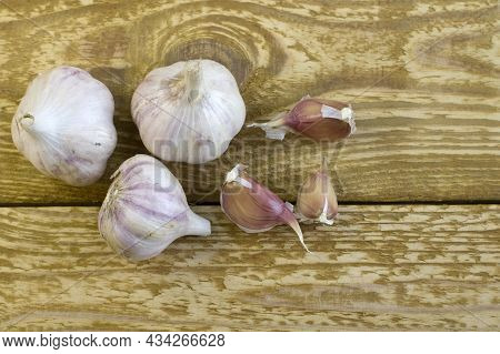 Dried Garlic On Glass Plate Close Up Flat Lay Photo On Brown Textured Wooden Background Top View