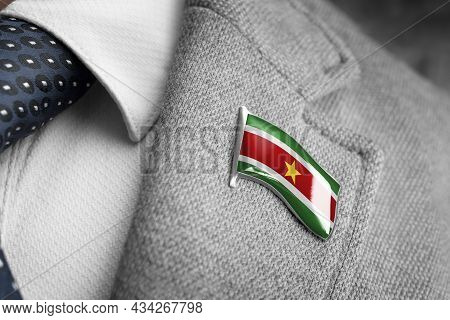 Metal Badge With The Flag Of Suriname On A Suit Lapel