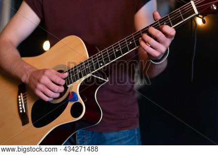 Male Musician Playing Acoustic Guitar. Guitarist Plays Classical Guitar On Stage In Concert Handsome