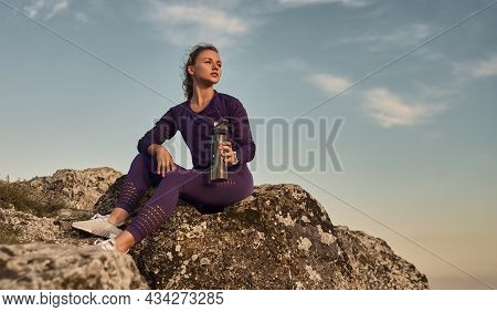 Low Angle Full Length Of Relaxed Young Female In Sportswear With Metal Bottle Of Water, In Hand Cont