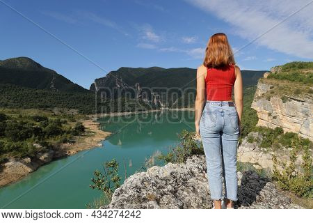 Back View Full Body Portrait Of A Woman In Red Standing Contemplating A Lake
