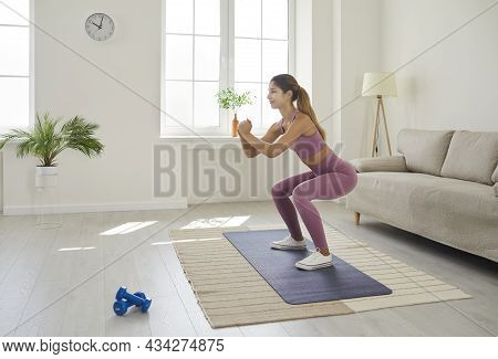 Happy Fit Young Woman In Sportswear Doing Squats During A Fitness Workout At Home