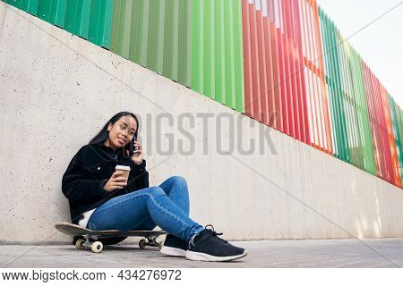 Asian Teenage Girl Talking By Phone Outdoors Sitting On Her Skateboard Leaning Against A Concrete Wa
