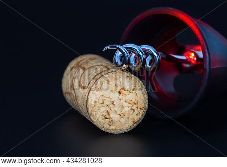 Corkscrew And Wine Stopper On A Dark Background With Red Reflexes.
