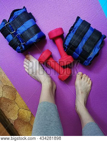 Equipment For Exercising The Muscles Of The Arms And Legs. Weights, Sandbags And Female Legs