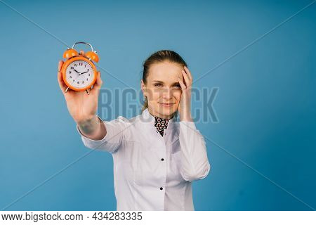 Young Beautiful Doctor Woman In Lab Coat, Studio Shot, Blue Background