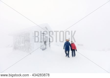 Family of father and daughter walking next to snow covered hut on winter day in Lapland Finland