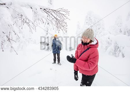 Family of father and daughter having fun playing in snow covered winter forest in Lapland Finland