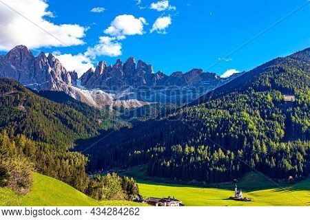Dolomites on a sunny autumn day. The sunny bright day. The beautiful village in the Dolomites Santa Maddalena. Charming old little church in the Val de Funes