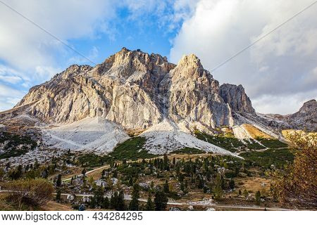 The majestic pass in the Eastern Alps of Falzarego. Picturesque sunset in the colorful rocks of the Dolomites. White and gray dolomite rocks. The clouds are flying across the sky