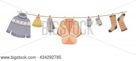 Knitted Clothes On Rope. Knit, Wool Thread Cardigan And Sweater. Knitting Accessories, Mittens And W