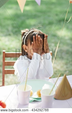 Cute Little Girl At Picnic Table Outdoors Decorated With Balloons For Birthday Party In Summer