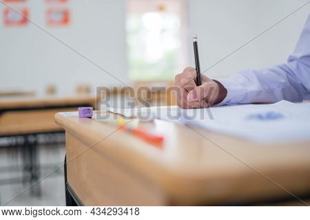 Asian Students Testing In Exam Exercise Taking At High School Or University In Test Room. Hands Hold