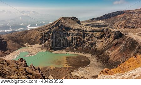 An Amazing Turquoise Acid Lake In The Crater Of A Volcano. High Steep Slopes. There Is Snow On The B