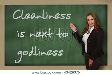 Teacher Showing Cleanliness Is Next To Godliness On Blackboard