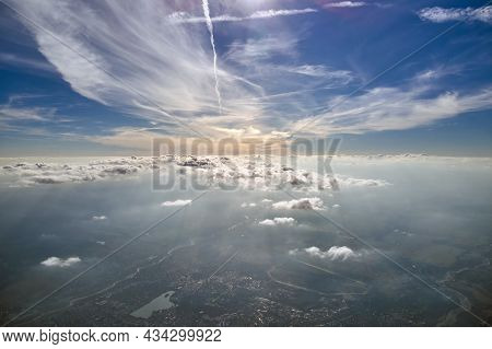 Aerial View From Airplane Window At High Altitude Of Distant City Covered With Layer Of Thin Misty S