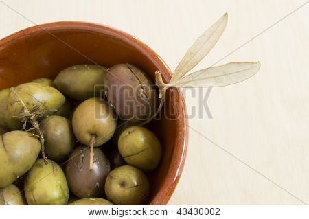 green spanish olives in a ceramic container