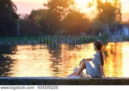 Back View Of Lonely Young Woman Sitting Alone On Lake Shore Enjoying Warm Evening. Wellbeing And Rel